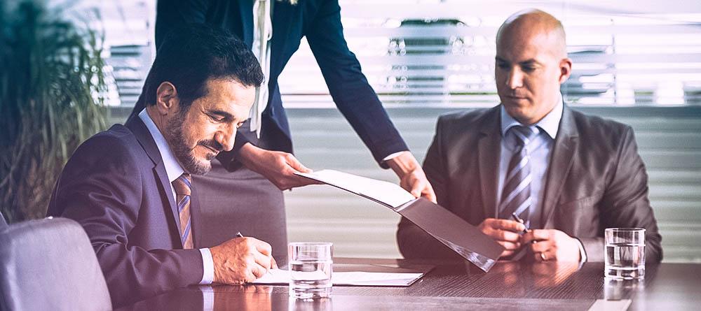 Businessmen signing document