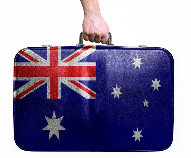 Tourist hand holding vintage travel bag with flag of Australia