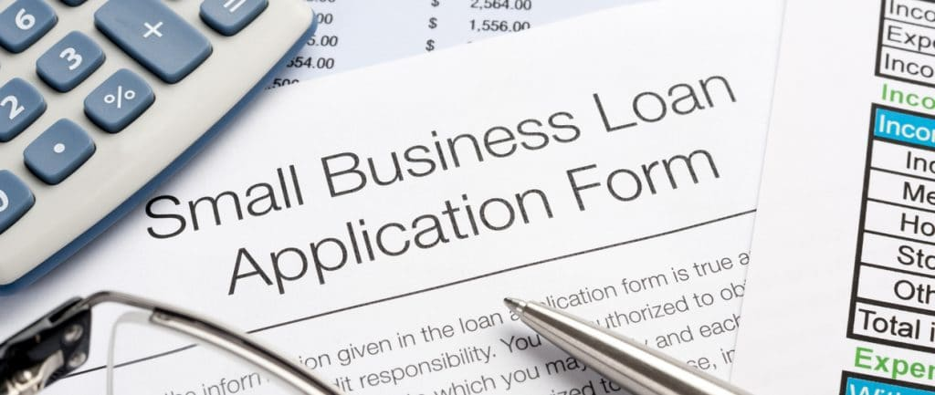 Small Business Loan Application Form With Pen, Calculator